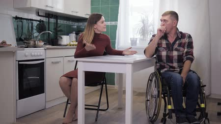 desfocado : family crisis, unhappy relationship of a disabled person in depression in a wheelchair stressful situation with an aggressive wife screaming and waving hands