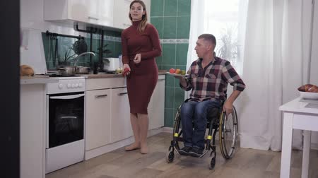 cripple : family relationship, happy husband in a wheelchair has fun with his wife cooks in the kitchen