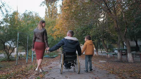 inwalida : family relationships, happy disabled person in wheelchair enjoys life together with a child and his wife raise their hands up while walking on beautiful autumn afternoon, rear view