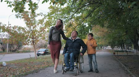 inwalida : family support, disabled husband in a wheelchair walks with his family on beautiful fall day through city streets