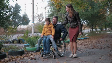 inwalida : family walk, disabled father in a wheelchair carries his son on his knees walking in the autumn street with his smiling wife Wideo