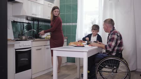 cripple : friendly family, male father in a wheelchair in the kitchen at the table preparing dinner with his son and wife, talking nicely and laughing