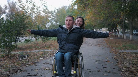 wachter : friendly support, happy disabled man have fun on a wheelchair ride a smiling female in autumn park
