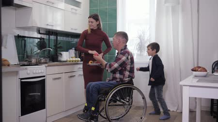 inwalida : hanging with family, man in a wheelchair enjoys a happy pastime with his wife and child in the kitchen while cooking