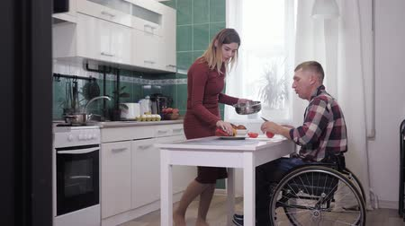 paralysé : happy couple, joyful man in a wheelchair have fun with his wife while cooking in his kitchen Vidéos Libres De Droits