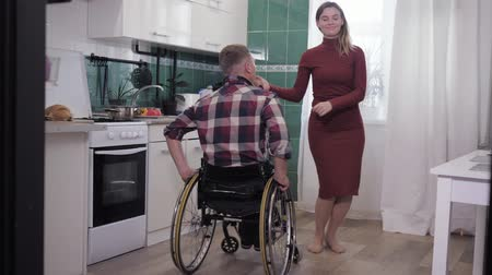 attitude : happy family, invalid man in wheelchair is dancing with his wife in his kitchen while cooking