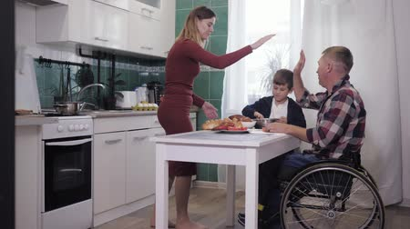 idílio : happy parenting, disabled father has fun with a loving wife and a happy son while cooking for his family