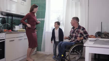 attitude : joyful father disabled person with his wife and son have fun cooking in the kitchen, family relationships
