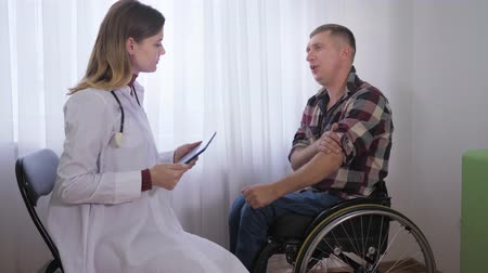 inwalida : male patient in wheelchair during medical examination tells his health problems to a female doctor