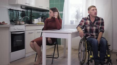 inwalida : quarrel in the family, upset husband, disabled person in a wheelchair, curses with his stubborn sad wife in the kitchen, family scandal