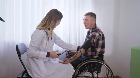 reklamacja : social worker during a physical examination measures pressure with a professional tool to a patient in a wheelchair Wideo