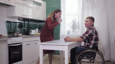 nervous breakdown : unhappy disabled man in wheelchair in stressful situation finds out relationship with his nervous wife, waving his hands aggressively background of kitchen in apartment.