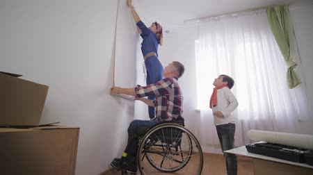 paralysé : beloved husband disabled person in wheelchair with his friendly family, chooses new wallpaper for the repair room Vidéos Libres De Droits