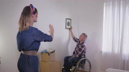 inwalida : disabled husband in a wheelchair chooses a place for a framed picture on a white wall while her cute wife makes the shape of a frame out of fingers, interior details