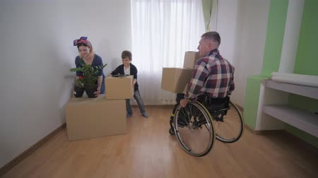 inwalida : family moving, father with disabilities in wheelchair with his smiling wife and cheerful son settles in and enjoy the new apartment Wideo