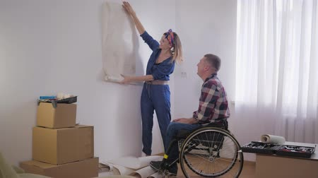 amado : family relationships, beloved disabled man in a wheelchair with a caring, smiling wife chooses wallpaper in a new interior during repair Stock Footage