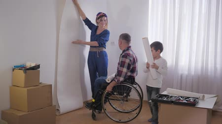 paralysé : friendly family, beloved disabled father in wheelchair with caring wife and a wonderful child chooses wallpaper in new interior during repair Vidéos Libres De Droits