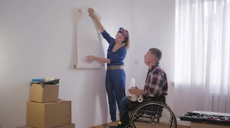 paralysé : happy couple disabled man in wheelchair with young beautiful woman chooses new interior in bedroom during repair