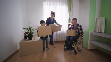 plezant : happy family with a disabled father in a stroller with boxes in hand stands in a new apartment and discusses the arrangement of furniture in room, social assistance Stockvideo
