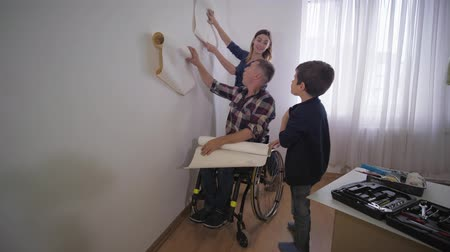 paralysé : happy family, cheerful little son with his disabled father and his beautiful mother chooses wallpaper in his room during repair