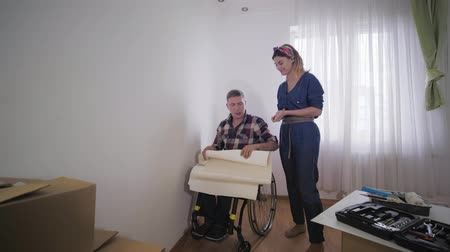 cripple : happy married couple disabled husband in a wheelchair and young wife chooses beautiful wallpaper in room during repair Stock Footage