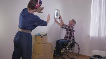 relocate : helpful disabled, person in wheelchair hangs picture while his wife makes a frame with her fingers and chooses a place for the image on a white wall