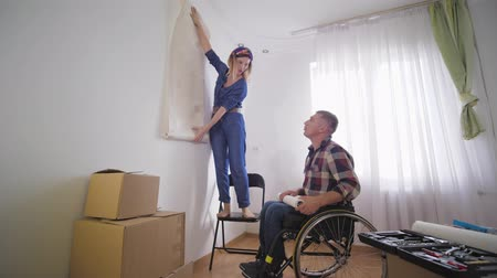 inwalida : repair in new apartment, happy father and disabled person in wheelchair with his wife and joyful son choose new wallpaper in bedroom