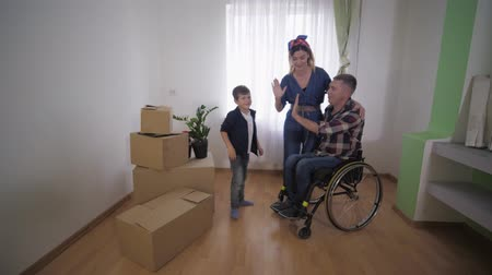 plezant : young family, disabled father in wheelchair happy moving and discusses furniture arrangement in new apartment on background of an empty wall with window and boxes