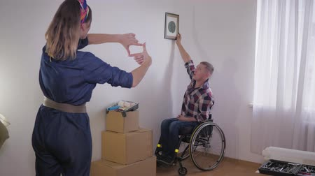 ремонт : Young happy couple with husband in a wheelchair moved to their new home and hung the decor on a white wall Стоковые видеозаписи