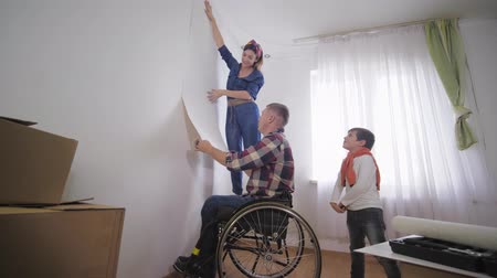 paralysé : young happy family happy father and disabled person in wheelchair with his wife and joyful son are choosing new wallpaper in room during repair