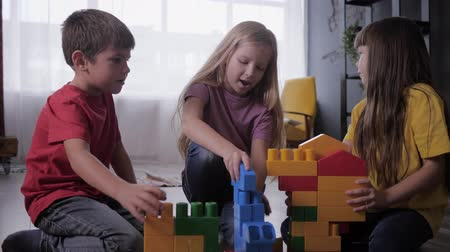 construtor : creative games for children, happy little ones enthusiastically play with developing constructor build original designs from colorful blocks