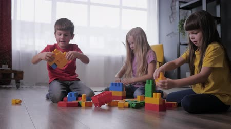 ロジック : joyful children play educational games, build toys from colored blocks of the designer