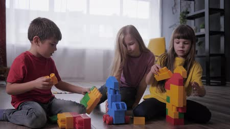construtor : relationship of children, charming girlfriends and a cute boy together play educational toys with colorful blocks during a kids party