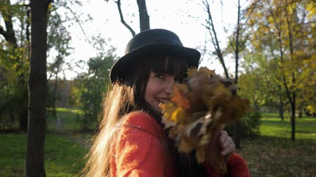 fleet : portrait of smiling girl in hat with long hair, she holds friend hand and leads him through sunny autumn park on walk during season of fallen leaves Stock Footage