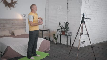 behulpzaam : attractive old man shows wellness exercises recording videon smartphone for social networks and followers in a cozy room with a designer interior
