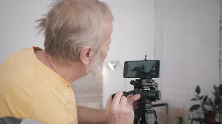 telefonia : elderly man and technology, modern grandfather is socially active and has his own blog sets up a camera on a smartphone in his room to record new content