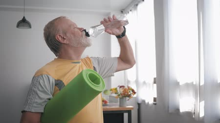 daadkracht : handsome elderly man with a beard after playing sports holds a yoga mat in his hands and drinks clean water to restore water balance in the body, taking care of his health Stockvideo