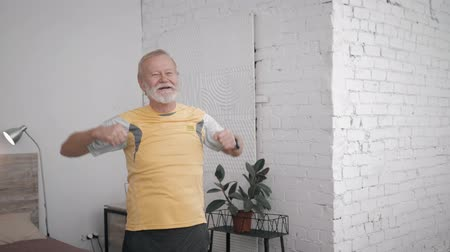 physically : happy grandfather athlete leads an active and healthy lifestyle doing useful exercises to maintain vitality in his room with a creative interior