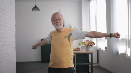 peppy : Health care, an elderly attractive man goes in for sports and performs exercises to improve the body, makes a helpless gesture and turns from side to side while indoors