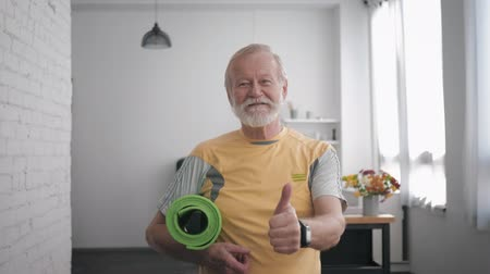 peppy : health care, handsome smiling old man in great shape with a yoga mat in his hands and a smart watch after playing sports to maintain health and showing a thumbs up gesture while standing indoors again