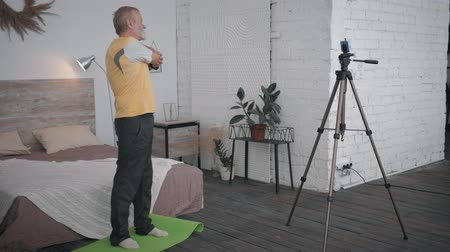 telefonia : Influencers blogger, aged man shows an exercise for joints on a phone camera recording a sport vlog for social networks and followers in his room