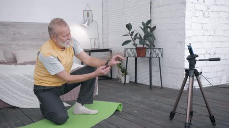 ajánlás : Influencers blogger, old man takes a review of smart watches for vlog recommending to his audience of subscribers a device sitting on a yoga mat in a room with a modern interior
