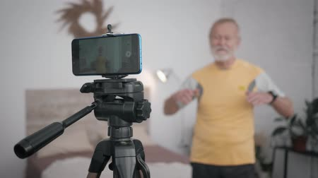 учение : modern elderly male blogger maintains a blog about a healthy lifestyle and records video on a mobile phone in the room during a live broadcast Стоковые видеозаписи