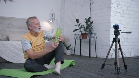 recomendacion : old blogger, aging man Influencers love sports takes a drink review on a smartphone for vlog recommending water to his subscribers during sitting on a yoga mat in creatives interior Archivo de Video