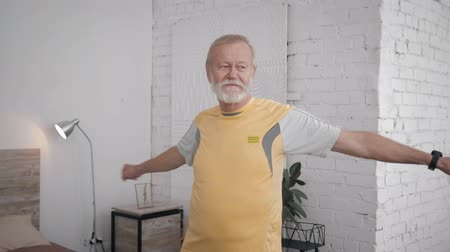 заботливый : old handsome man leads a healthy lifestyle and does useful exercises for health and vitality in his room with a creative interior Стоковые видеозаписи