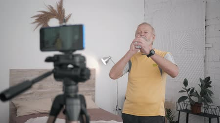 fikirler : old man Influencers blogging on healthy lifestyle content recording exercises on the phone camera during a live broadcast
