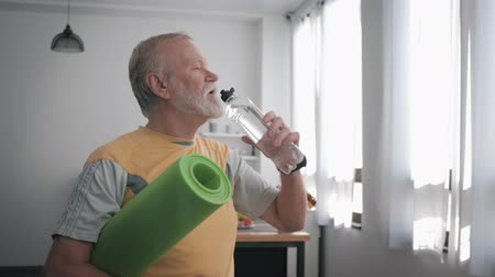 daadkracht : old man leading a sporting lifestyle takes care of his health and drinks clean water, while standing on indoors with a beautiful interior and holds a yoga mat in his hands Stockvideo
