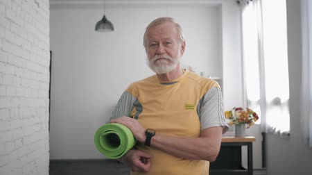 stary : Portrait of a handsome elderly man, with a yoga mat in his hands and a smart watch after playing sports to maintain his health standing in a room against a beautiful interior