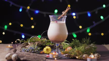 küçük hindistan cevizi : beautiful cocktail glass with a traditional egg drink on the background of a Christmas tree and lights, season eggnog Stok Video