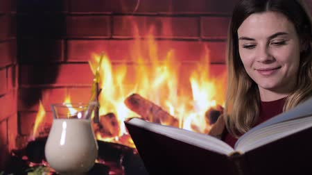 pigtailler : beautiful young girl reads christmas stories in a book near a traditional cocktail eggnog against a fire by the fireplace Stok Video